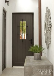 Strategically painted dark gray, the exterior doors counterbalance the crisp white walls and exposed copper piping.