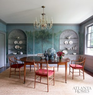 The dining room, which features original Georgian-inspired alcove cabinetry by Shutze, is enlivened with a mural by Atlanta-based Ray Goins. The antique French Directoire table is from Karla Katz; the Venetian glass chandelier is from Foxglove Antiques & Galleries.