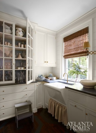 In the butler's pantry, a fabric curtain conceals the storage space beneath the reclaimed sink.