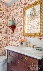 Mathison Glenn elevated the simple powder room with a marble-topped antique vanity and a Pierre Frey wallpaper featuring a whimsical meandering chinoiserie print.
