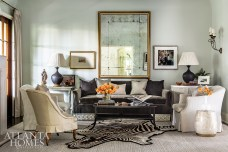 """Originally the living room featured existing pieces in neutral tones, but Bromenschenkel quips, """"It was about as exciting as a bowl of oatmeal. It needed contrast."""" That meant reupholstering furniture in light-reflective fabrics and introducing a giant antique mirror framed by Myott Studio to make the space appear larger and more welcoming."""