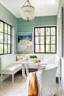 Centered around a photograph of a beach in Southern Portugal by Christian Chaize through Jackson Fine Art, the breakfast room drew inspiration from natural elements. A turquoise grasscloth wallcovering by Phillip Jeffries mimics ocean hues, while windows allow for views of the surrounding trees.