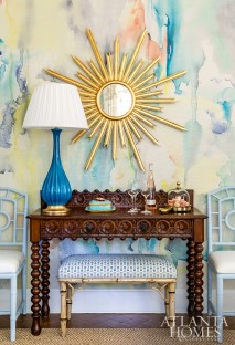 In the dining room, a brilliant symphony of color, periods and styles are represented thanks to a contemporary gilt sunburst mirror, a treasured antique sideboard and Midcentury lamp sourced from Parc Monceau.