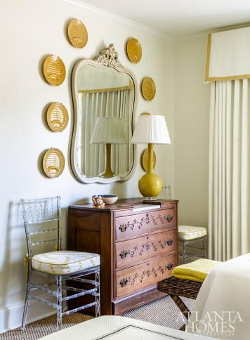 Pelmets above the beds and window provide architectural detailing in the guest bedroom, where a set of asparagus plates hangs over a French chest, a treasured family antique.
