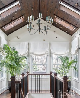 The newly added solarium's walls are adorned with custom porcelain and gilded butterflies by Charlotte Smith Studios—a nod to Inman Park's butterfly logo. The chandelier is by Visual Comfort through Circa Lighting.