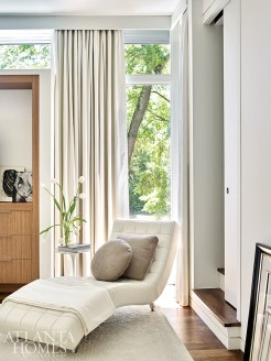 Upholstered in white leather, a modern chaise lounge offers a spot to relax and read in the ethereal, light-filled master bedroom.