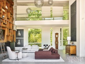 A pair of paintings by Todd Murphy and a vertical triptych by Joseph Guay add another layer to the open living room, where a sectional sofa by Minotti anchors a cozy seating area in front of the fireplace.