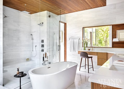 Inspired by the wood often used in boats, a teak ceiling adds a warm quality to the white marble and porcelain tile in the master bathroom.