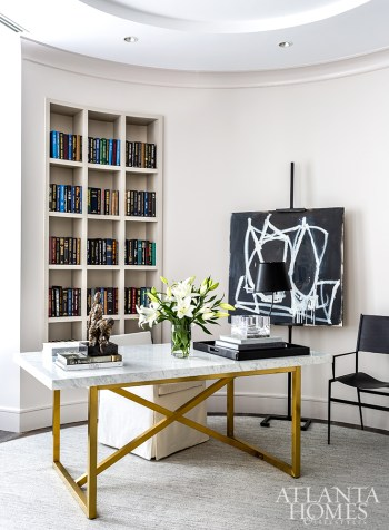 Displayed on an easel, an abstract painting by Sylvia McEwan through Pryor Fine Art juxtaposes a brass desk with a marble top. The black chair is by David Iatesta.