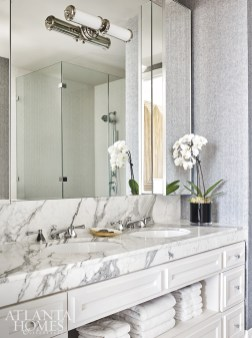 Reminiscent of men's suiting, the wallcovering by Holland & Sherry complements the thick marble in the master bathroom.