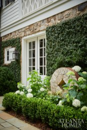A striking millstone garden ornament is set off by 'Annabelle' hydrangea and American boxwood.