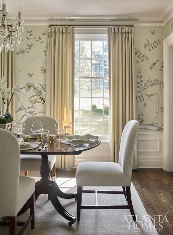 "A silk wallpaper by de Gournay through Ainsworth-Noah makes an impact in the dining room and serves as an anchoring color scheme for the rest of the home. ""It was one of the first things we looked at and with that being such an important room, I wanted it all to flow,"" says Bradley. The dining table is from the early 19th century and was sourced from Alain Michel Wholesale Antiques, a dealer in Brussels, Belgium, who the homeowners met when living there in the early 2000s. The chandelier is antique."