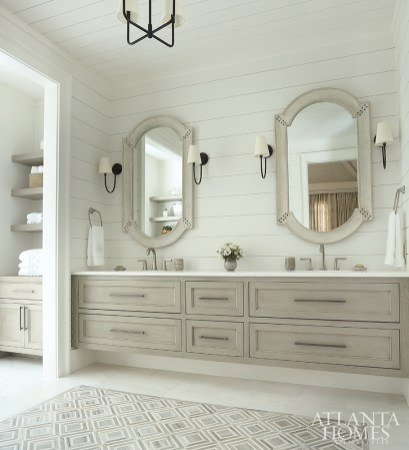 Shiplap walls lend a tailored cabin feel while bleached wood mirrors with rivet detailing add rustic elegance.