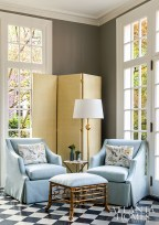 A three-panel upholstered screen, matching lounge chairs by Charles Stewart and a bamboo ottoman create an inviting vignette in the light-filled sunroom.