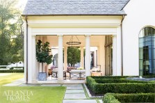 Furnishings by Michael Taylor and Formations and a sizable fireplace ensure the covered loggia is just as comfortable as the adjacent family room.