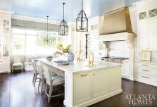 A blue-painted ceiling and a brass hood by Francois & Co. punctuate the classic white cabinetry in the kitchen. The counter stools are by Mattaliano.