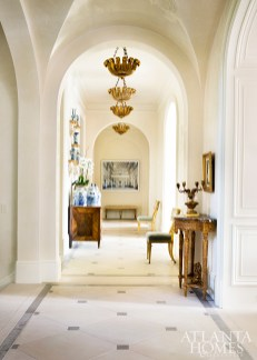 Gilt pendants by Paul Ferrante through Ainsworth-Noah call attention to the arched ceilings in the hallway, which is furnished with a 19th-century Italian chest from William Word Fine Antiques and 1930s Swedish chairs from Maison Felice.