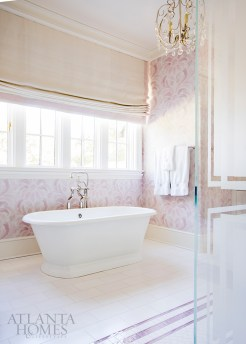 A damask wallcovering from Designers Guild ties in with the floor tile in the teenage daughter's en-suite bathroom, which is illuminated by a brass chandelier from Circa Lighting.