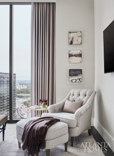 In the master suite, a tufted chair and ottoman from Hickory Chair offers a spot to enjoy the city views.