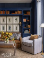 A custom built-in bookcase frames a tailored corduroy-covered sofa from Lee Industries in the library-like den. The swivel chair is by Mr. & Mrs. Howard for Sherrill Furniture.