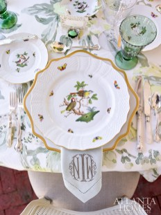 Herend Rothschild Bird china sings against the gilt-rimmed chargers and monogrammed napkins by Gramercy. Family heirloom silver flatware mixed with mother-of-pearl pieces complete the elegant setting.