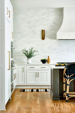 In this serene but sophisticated kitchen environment, texture, tone and clean lines are the focal points. An absence of upper cabinets and an all-white palette are balanced by wood and brass accents.