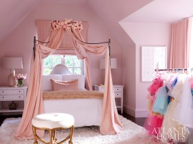 Inspired by her love of princesses, the young daughter's bedroom features pink walls, a canopy bed from RH and white nightstands from CFC. The rug is by Surya, and the drapery fabric is by Fabricut.