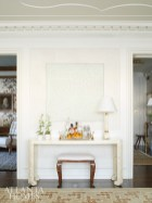 A console from Parc Monceau, along with a painting by Paolo Ceribelli, make for an elegant bar set-up in the living room.