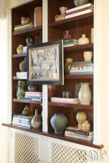 A bookcase in the foyer displays the couple's collection of midcentury pottery.
