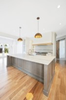 An inviting kitchen with sophisticated natural quartzite, a dual-fuel range by Wolf and a custom hood.