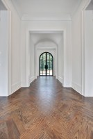 An entry hall with harmonious barrel vault ceiling, herringbone hardwood flooring and imported arched steel doors by French Steel.