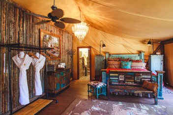 A safari-style glamping tent includes plush linens, heated floors, air conditioning and plumbing.