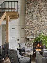 Made with stones sourced in nearby North Carolina, the fireplace lends a cozy spot to relax after a long day on the lake. The iron chairs are by Bernhardt.