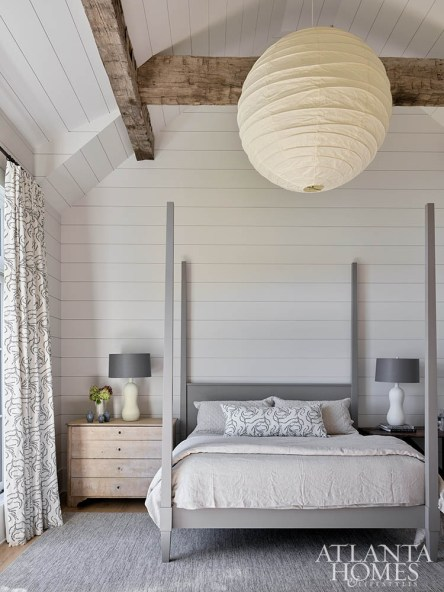 A large Noguchi paper lantern creates a soft glow in the master bedroom, which is furnished with a custom painted four-poster bed. The matte ceramic table lamps are by Currey & Company.