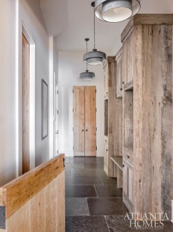 Located just off the kitchen, the generously sized mudroom is outfitted with weathered galvanized metal pendants from Generation Lighting and reclaimed oak cabinetry.
