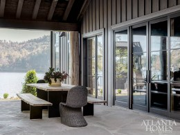 On the covered porch overlooking the water, a pair of woven host chairs from B.D. Jeffries play off the steel-and-wood dining set from AuthenTEAK.
