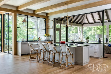 The kitchen's custom taupe-gray cabinetry by Phoenix Millworks plays up the home's calm and airy appeal. Light pendants from Visual Comfort hang over the central island and Serena & Lily barstools offer a casual spot for quick meals.
