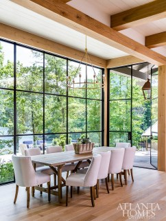 An oversized dining table provides ample room for hosting family and friends while a Visual Comfort chandelier hangs high so as not to detract from the vista.