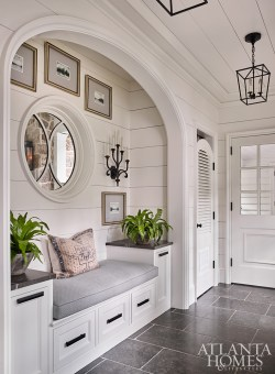 """A mudroom hallway """"makes it easy during wet days—for both the family and their dog,"""" says Bozeman. The pillow is through Foxglove Antiques & Galleries and the artwork is from Peachtree Battle Antiques & Interiors."""
