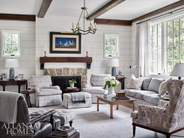 In the living room, beamed ceilings add rustic texture. The sofa and armchairs are both through Travis & Company, upholstered in Mark Alexander fabric.