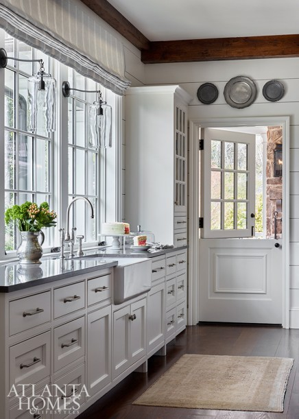 Wall-to-wall cabinetry helps keep kitchen clutter at bay, while a dutch door allows the summer breeze inside. The pewter plates are through Foxglove Antiques & Galleries and Peachtree Battle Antiques & Interiors.