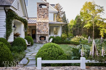 Stepping stone paths and an outdoor fireplace echo the home's farmhouse charm, while a mix of perennials, herbs, boxwoods, foxglove, African blue basil and hydrangeas add a sense of softness.