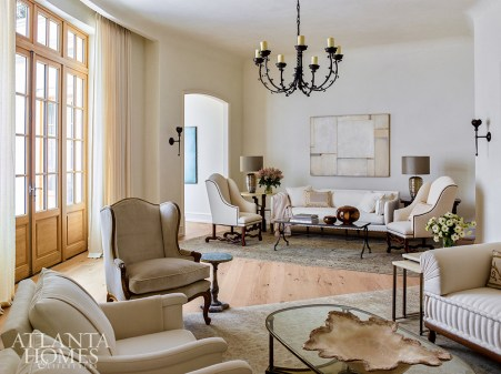 A salon-style furniture layout with two distinct seating groups makes the most of the formal living room's unusual shape.