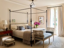 An iron four-poster bed with an upholstered headboard by Dessin Fournir through Ainsworth-Noah leans into Southern gentility in the master suite.