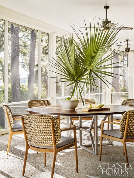 An outdoor dining area drinks in the natural daylight. The dining table is custom through Forsyth Metal Works and dining chairs through Gloster.
