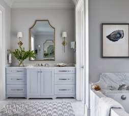 The clients didn't want a visible tub skirt, so the main bathroom's tub—built by Ralph Chapman of Creative Stone—was undermounted with the entire side made from Calacatta gold marble. In the center of the room, a marble herringbone pattern anchors the space.