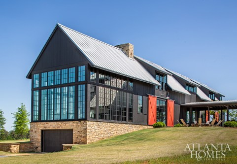 Floor-to-ceiling windows on the barn-like structure connect the interiors with countryside views. The doors are painted in Benjamin Moore's 1301 Spanish Red.