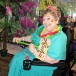 Senior lady in blue smiles coyly at camera during luau.