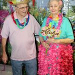 Married senior couple holds up Aloha sign before the dance.