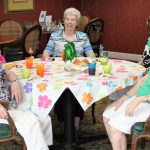 Resident senior in front of colorfully decorated table.